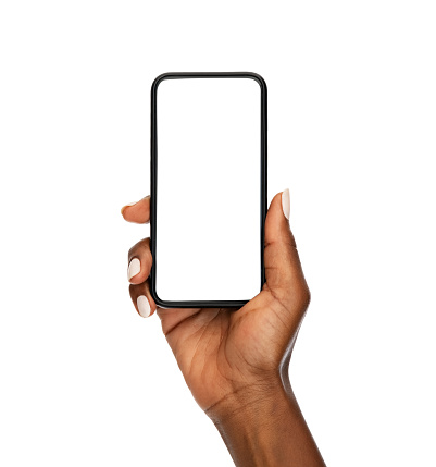 Close up of mature african woman holding smartphone with blank screen isolated on while background. Black woman hand showing empty screen of modern cellphone. Mature female hand showing white screen of mobile phone.