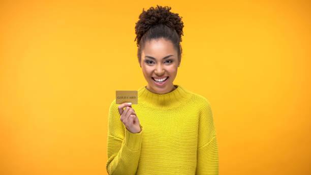 schwarze frau mit goldener kreditkarte, vip-bankprogramme für reiche menschen - grußkarte stock-fotos und bilder