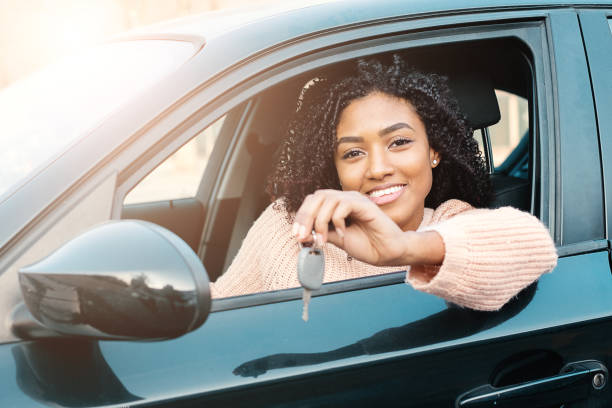 Black woman holding keys to new car and smiling at camera stock photo