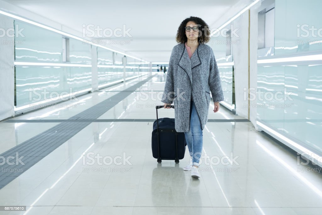 Black woman holding luggage ready to leave stock photo