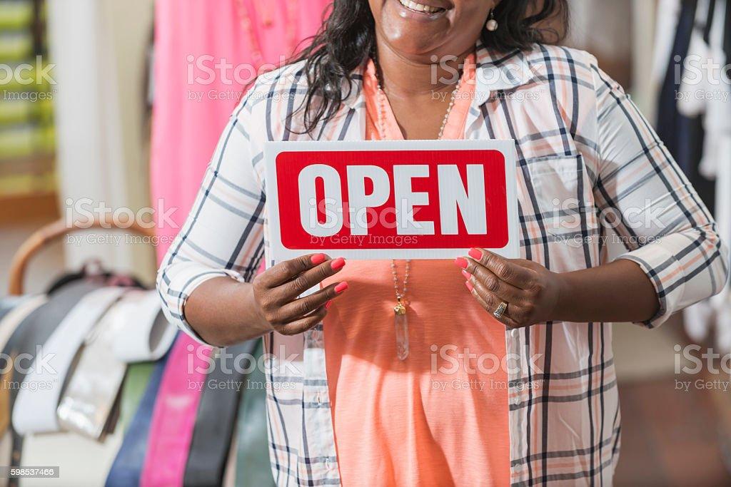 Noir femme tenant Panneau ouvert dans le magasin de vêtements photo libre de droits