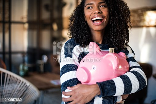 Black young woman hugging her pink piggy bank