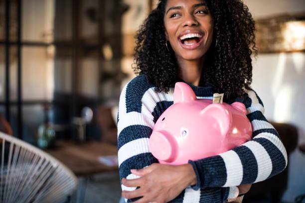Black woman hugging her piggy bank stock photo