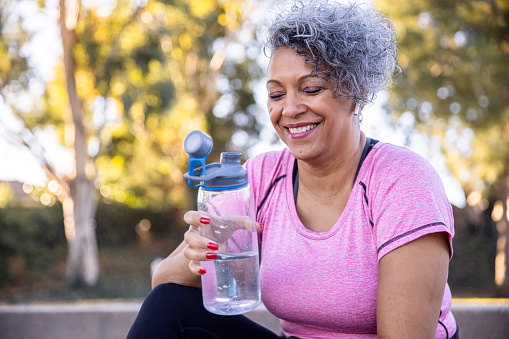 A black woman hydrating after her workout.
