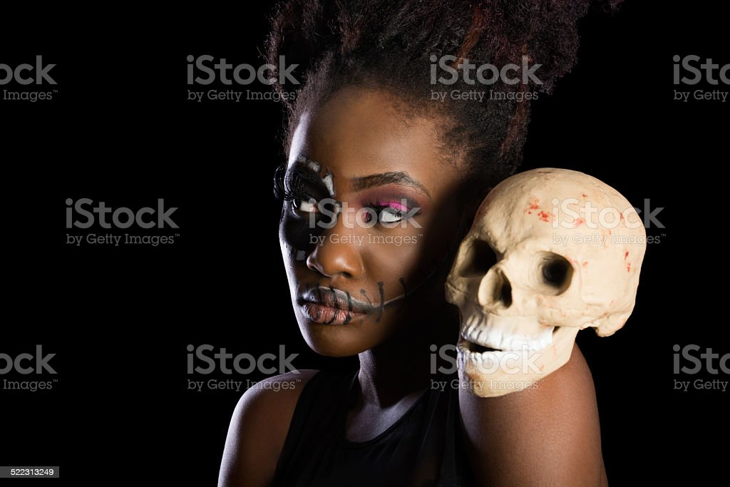 Black woman in sugarskull makeup, semi-profile with skull on shoulder. stock photo