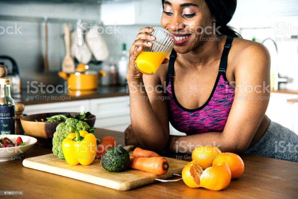 Black woman is drinking orange juice stock photo