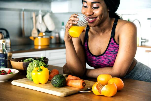 schwarze frau trinkt orangensaft - rawpixel woman stock-fotos und bilder