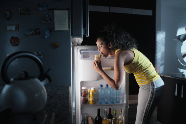 Black Woman Looking into Fridge For Midnight Snack stock photo