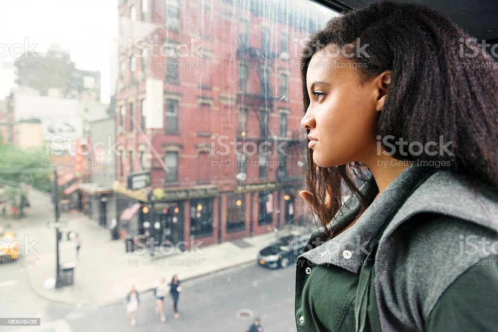 NYC Black Woman Looking Out Window at Urban City Streets royalty-free stock photo