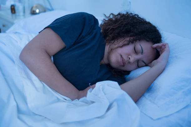 Black woman lying in bed trying to sleep stock photo