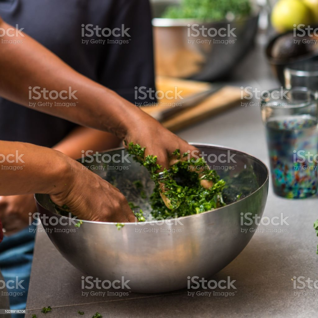 black woman mixing ingredients into salad stock photo