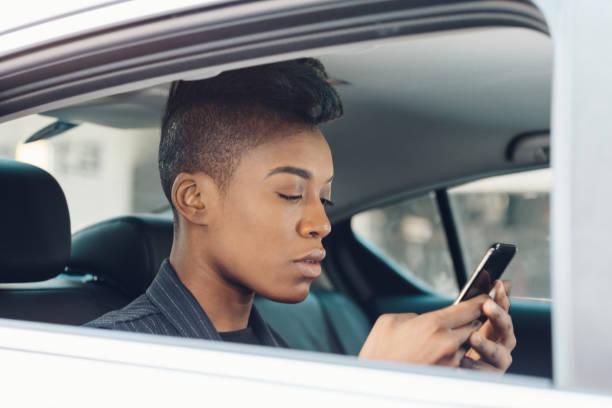 black woman on the phone using rideshare stock photo