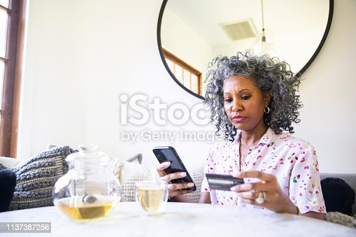 A black woman makes a purchase on her smartphone
