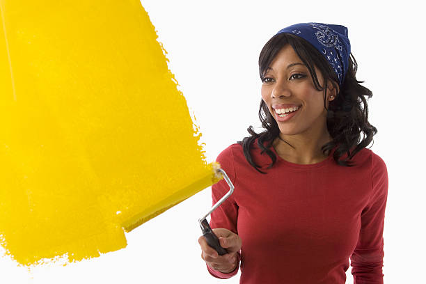 Black woman painting walls stock photo