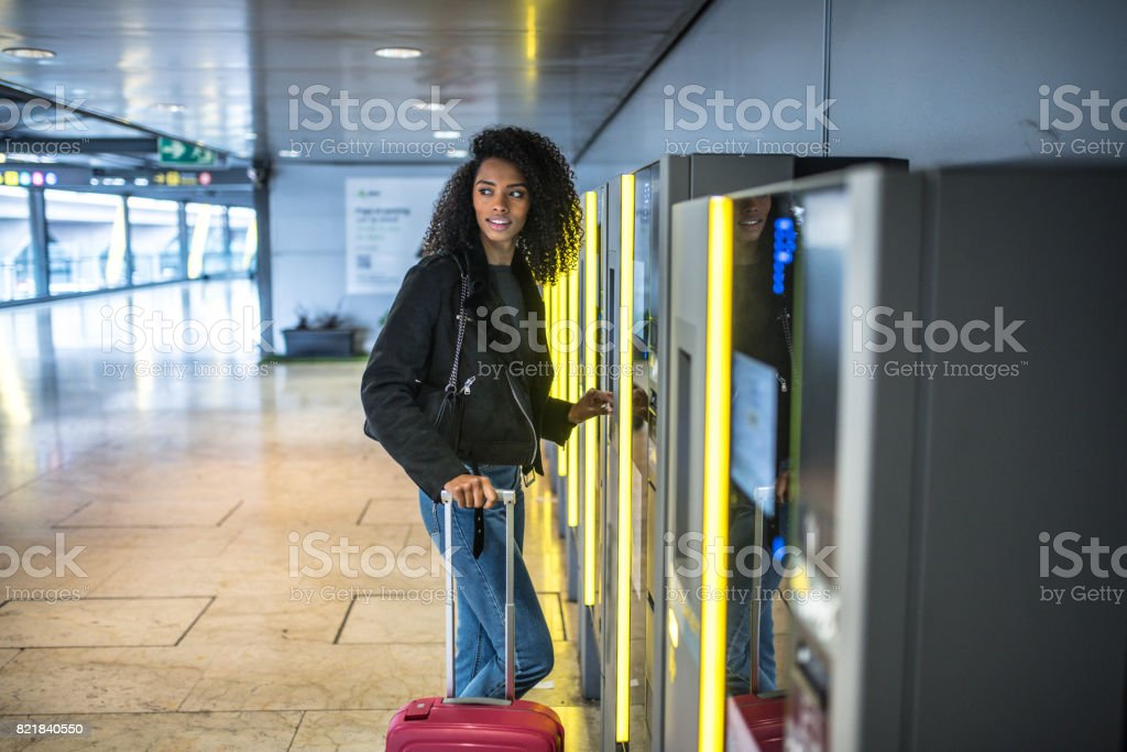 black Woman paying in the parking Machine in the airport with a suitcase stock photo