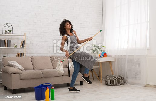 istock Black woman playing air guitar with mop 1080849666