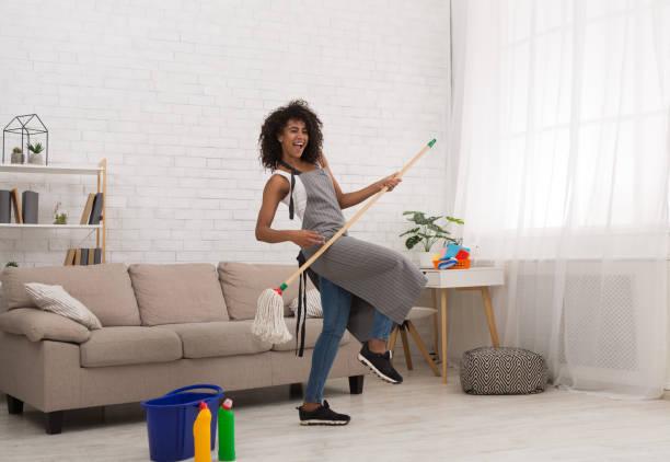 zwarte vrouw luchtgitaar spelen met mop - vrouw schoonmaken stockfoto's en -beelden