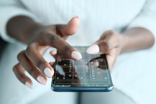 African American Woman Playing Sudoku Online For Brain Training, Using Mobile Phone. Cropped View, Closeup.