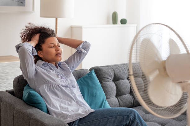 Black woman portrait cooling off at home during summer heat stock photo