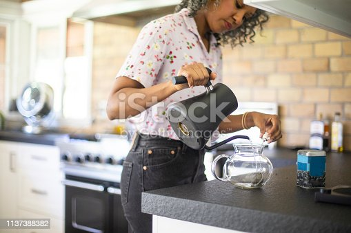 A black woman pours tea in her kitchen