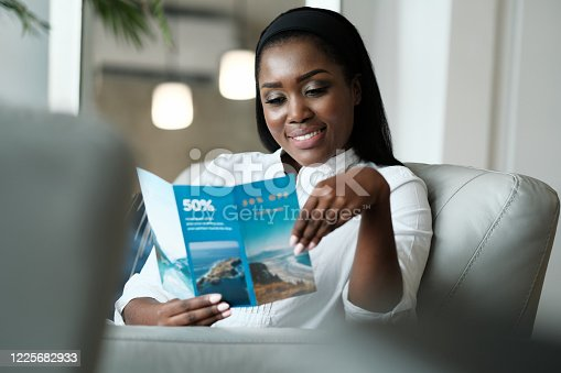 Black Woman Reading Travel Flyer For Holiday Trip