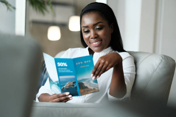Black Woman Reading Travel Flyer For Holiday Trip stock photo