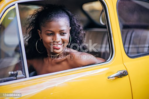 One beautiful young woman, black woman, sitting in the driver's seat of a car.