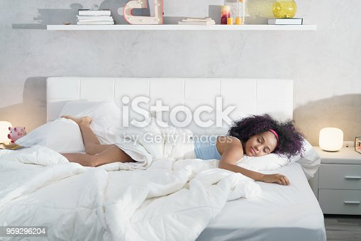 Young African American woman waking up at home. Portrait of happy black girl smiling, enjoying a large king size mattress all for herself.