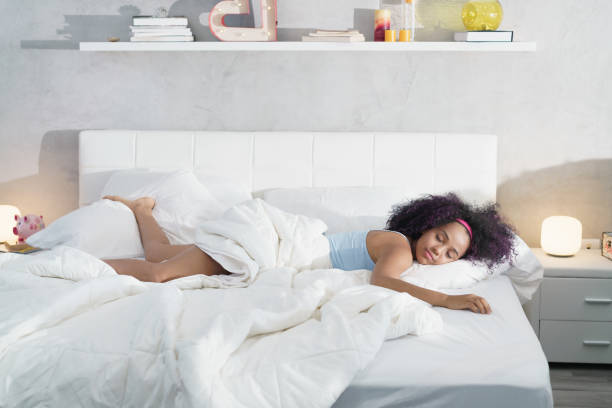 Black Woman Sleeping Alone in Large Bed stock photo