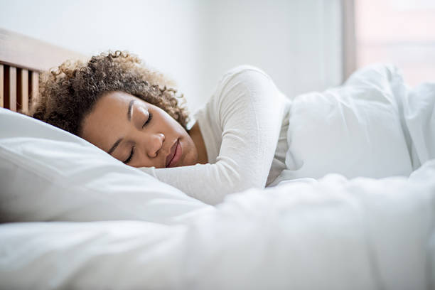 Black woman sleeping in bed stock photo