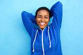 istock black woman smiling against blue wall with hands behind head 857924804