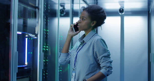 black woman speaking on phone in server room - call center стоковые фото и изображения