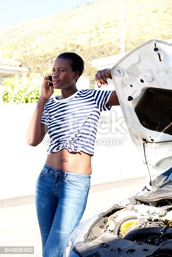 860373412 istock photo black woman standing by broken down car and calling for assistance on mobile phone 944698450