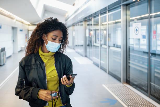 Black woman traveling on public transport and wearing face mask during coronavirus pandemic stock photo