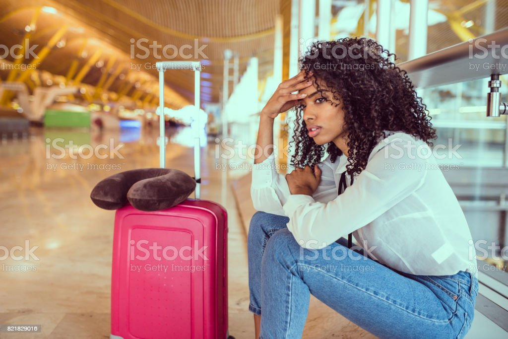 black Woman upset and frustrated at the airport with flight canceled stock photo