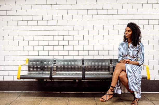 Black woman using mobile phone at london underground stock photo