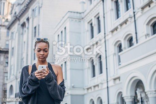 909457386istockphoto Black woman using phone on the street 1168569730