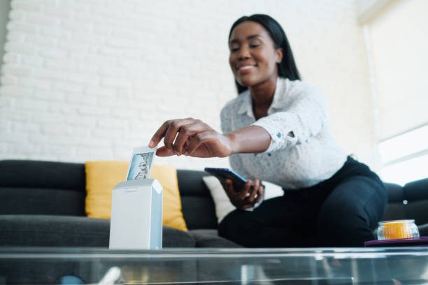 Black Woman Using Portable Wi-Fi Printer For Printing Pictures stock photo