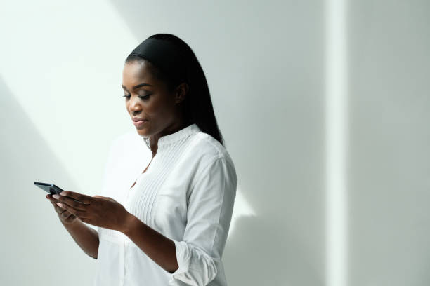 Black Woman Using Smartphone To Send Text Message stock photo