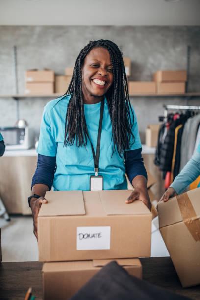mulher negra voluntária embalando caixas de doação em banco de alimentos beneficente - charity and relief work - fotografias e filmes do acervo