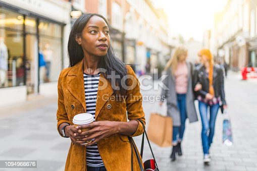 Black woman with two girls behind shopping and walking in London. Three girls, multiracial group, having fun in the city while shopping. Best friends sharing happiness, lifestyle and friendship concepts