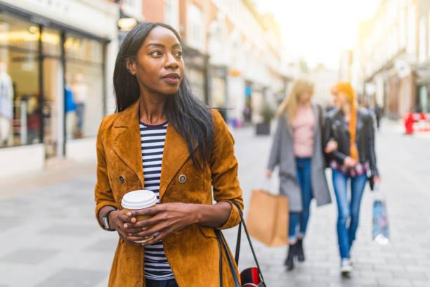 femme noire qui marche dans la ville, shopping thème - mode londres photos et images de collection
