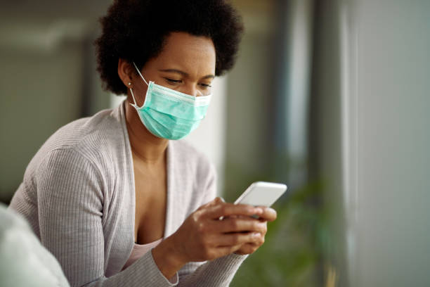 Black woman wearing face mask while text messaging on mobile phone at home. stock photo