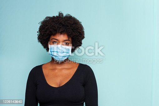 young woman wearing protection mask against covid-19 with blue background