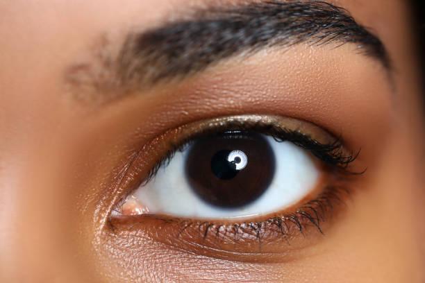 Black woman wide opened left eye stock photo