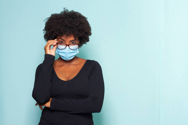 black woman with black power hair wearing protective mask wearing reading glasses - afro latino mask imagens e fotografias de stock