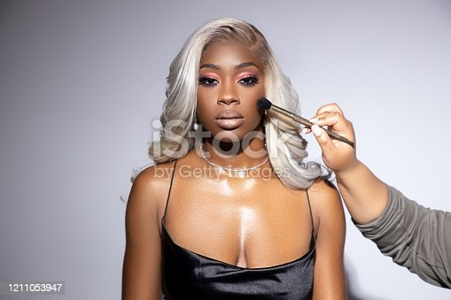 black girl with platinum blonde wig getting her make up done