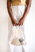 istock Black woman with knitted tote bag against white wall. 1167551433