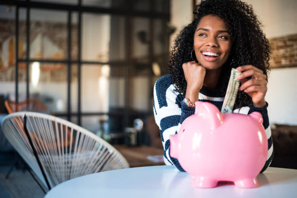 black woman with saving piggy bank - savings stock pictures, royalty-free photos & images