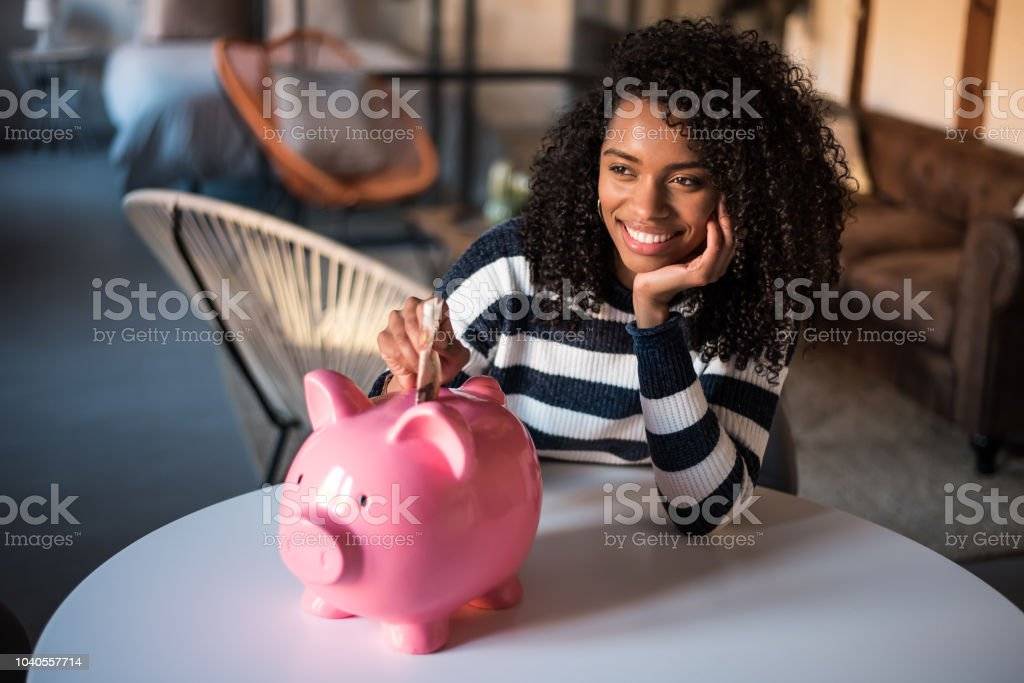 Black woman with saving piggy bank stock photo